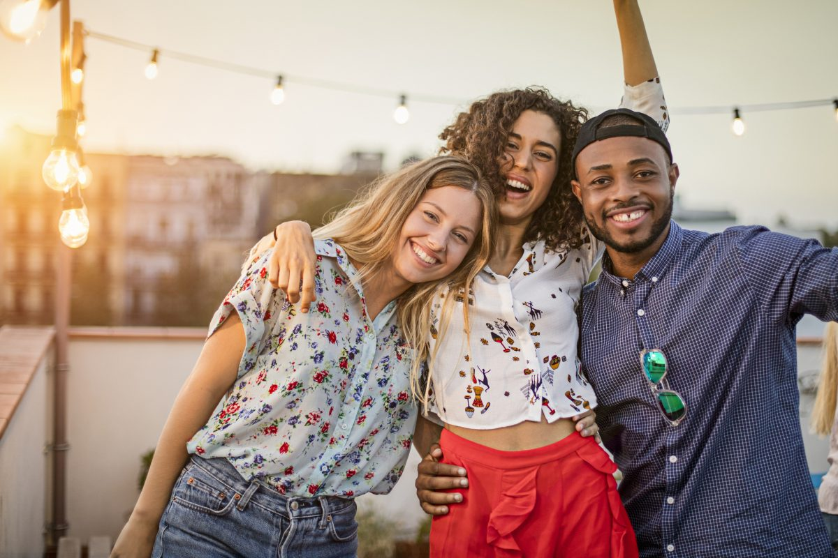 Portrait of happy multi ethnic friends enjoying on terrace. Smiling man and women are celebrating together during sunset. They are wearing casuals in party.