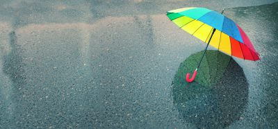 Colorful umbrella sitting on wet pavement