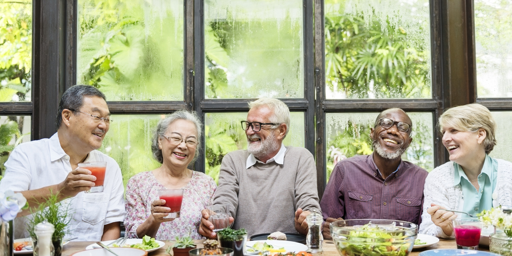 Group of elder adults enjoying a meal and laughing