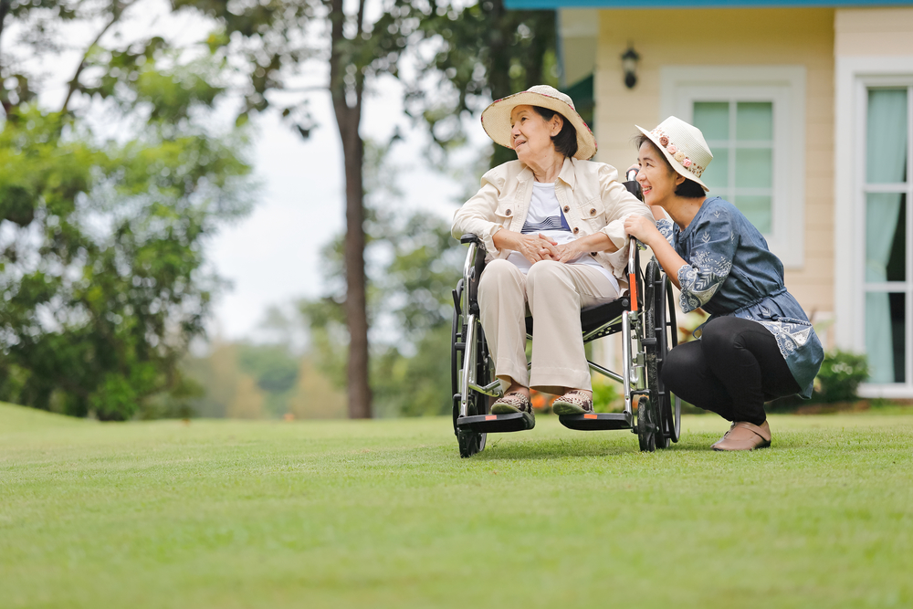 Image of a woman caring for another woman in a wheelchair